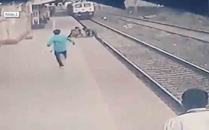 A man rescues a child in front of a speeding train in India